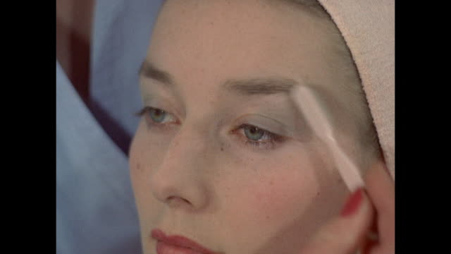 stockvideo's en b-roll-footage met 1961 - london - young women have makeup applied - 1961