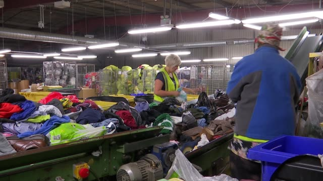 londoners discard 31 million items of clothing each year; uk, london, canning town; workers at clothing and textile recycling centre / ross barry... - clothing stock videos & royalty-free footage