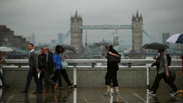 londoners walk across london bridge in rainy weather on the 16th of september 2016 - london bridge england stock videos & royalty-free footage