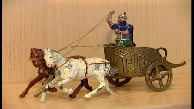london's museum of childhood reopens close up of toy lead soldiers on display roman gladiator in chariot with horses glass looking at train set in... - dondolarsi video stock e b–roll