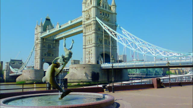 london's tower bridge serves as the backdrop to a riverfront fountain. - london bridge england stock videos & royalty-free footage