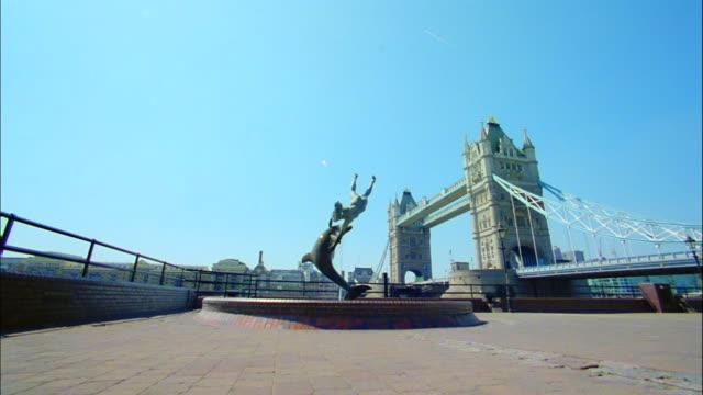vidéos et rushes de london's tower bridge serves as the backdrop to a riverfront fountain. - cétacé