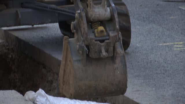london's victorian water network being upgraded; england: london: ext various of thames water workers working in road , digging in trench with digger - construction vehicle stock videos & royalty-free footage
