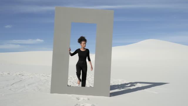 lone african american woman walks through desert doorframe, wide - ideas stock videos & royalty-free footage