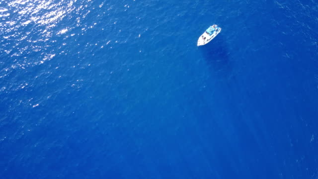 lone boat floating far below vantage of drone off maui coast - isole del pacifico video stock e b–roll