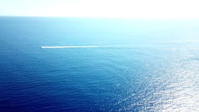 stockvideo's en b-roll-footage met lone boot reizen over de enorme uitgestrektheid van de oceaan voor de kust van maui - breed