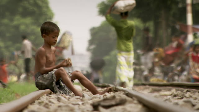 vídeos de stock, filmes e b-roll de a lone boy sitting on train tracks practices throwing and catching using stone ballast, dhaka, bangladesh. - bangladesh