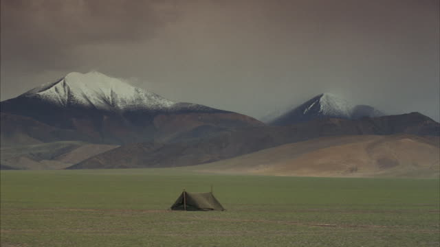 vidéos et rushes de a lone brown tent flaps in the wind in a green valley with snow-capped tibetan mountains in the distance. - tente