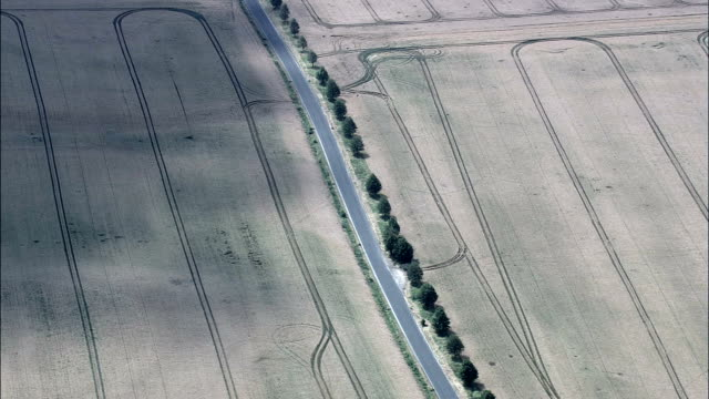 lone car crossing expanse of farmland  - aerial view - thuringia,  helicopter filming,  aerial video,  cineflex,  establishing shot,  germany - turingia video stock e b–roll