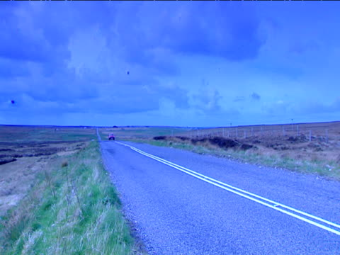 lone car drives down empty long straight road at dusk in remote countryside - 長さ点の映像素材/bロール