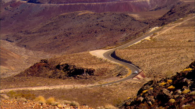ws, zo lone car on highway in death valley national park, california, usa - death valley national park stock videos & royalty-free footage