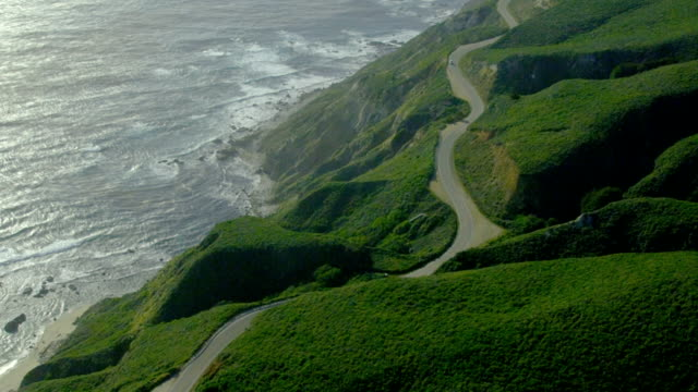 A lone car travels on a road at California's Big Sur along the cliffs over the Pacific coast.