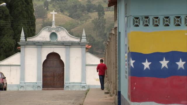 vídeos y material grabado en eventos de stock de ws zo lone figure walking towards small church in mountain village near venezuela-colombia border / near san cristobal, tachira, venezuela - venezuela