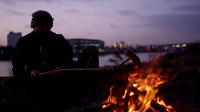 vidéos et rushes de homme seul feu feu de camp sur une rivière - viande