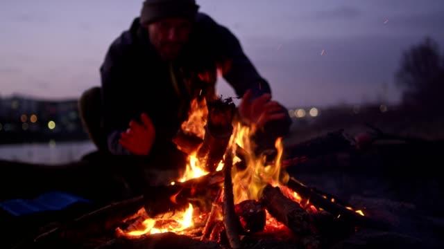 一人の男が、リバーサイドの上で焚き火を燃焼 - アウトドア点の映像素材/bロール