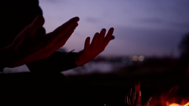 vídeos de stock e filmes b-roll de lone man burning campfire on a riverside. warming up hands - lareira