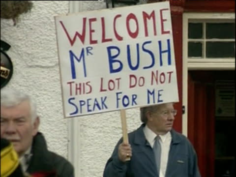 lone man holding placard reading 'welcome mr bush this lot do not speak for me' amidst anti war demonstration nov 03 - politik und regierung stock-videos und b-roll-filmmaterial