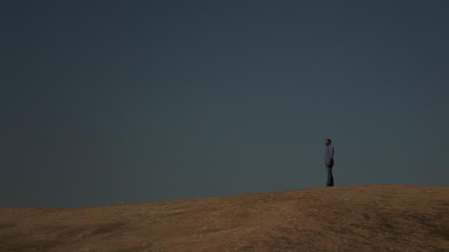 a lone man stands on a hill in the negev desert. - アラバ砂漠点の映像素材/bロール