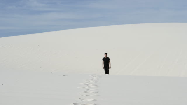 lone man walks in desert, wide - maglietta video stock e b–roll