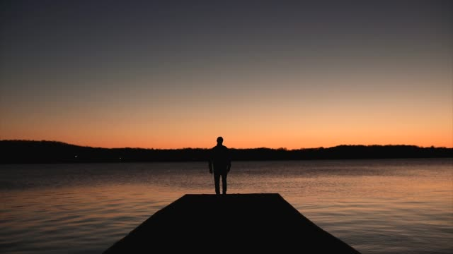 lone man walks on pier at sunrise in isolation while social distancing - in silhouette stock videos & royalty-free footage