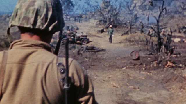 ha lone marine walking across battlefield passing scorched earth and wreckage toward fellow marines / iwo jima japan - schlacht um iwojima stock-videos und b-roll-filmmaterial