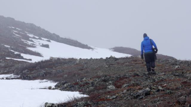 a lone photographer treks through the mist - paura video stock e b–roll