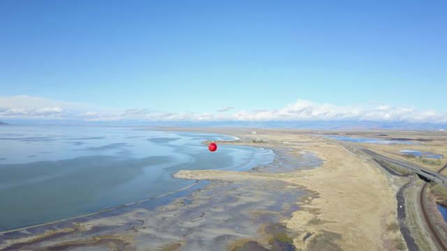 Lone red balloon floating high over the great salt lake