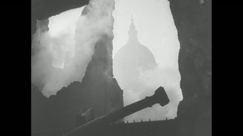 vidéos et rushes de lone, silhouetted firefighter climbs a long ladder and men with a hose spray water during the blitz of london / the dome of st paul's cathedral seen... - 1941