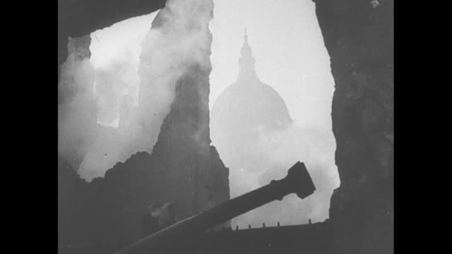 vídeos de stock e filmes b-roll de a lone silhouetted firefighter climbs a long ladder and men with a hose spray water during the blitz of london / the dome of st paul's cathedral seen... - ataque aéreo