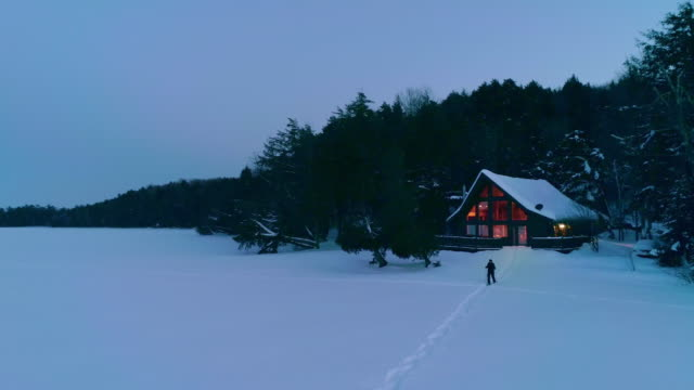 a lone snowshoer approaches / leaves a warm cabin on a frozen lake - コテージ点の映像素材/bロール