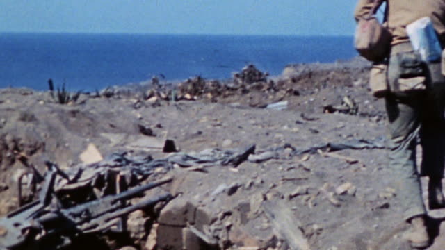 lone soldier walking across battlefield, carrying gear and passing burned out wreckage / iwo jima, japan - 1945 stock videos & royalty-free footage