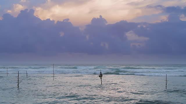 ws lone stilt fishermen (pole fishermen) casting for sardines and thunderhead cloud at sunset / ahangama, southern province, sri lanka - sri lankan culture stock videos & royalty-free footage