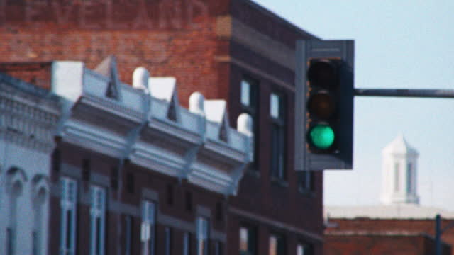 a lone traffic light changes from red to yellow to green in the downtown of a small rural community in the midwest the brick facades of main street in the background. - street name sign stock videos & royalty-free footage