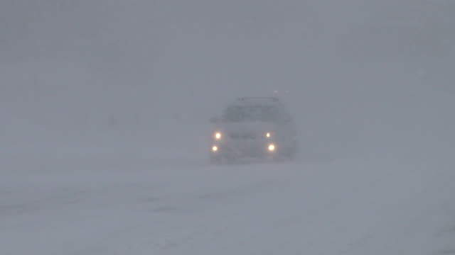 A lone vehicle travels slowly down a street in near whiteout conditions during a New England blizzard