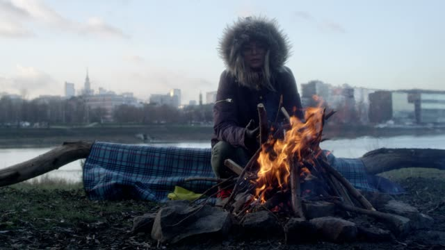 lone woman burning campfire on a riverside - bare tree stock videos & royalty-free footage