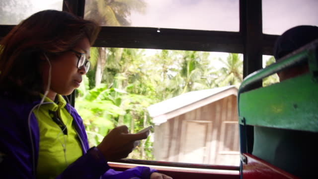 lone woman traveler from philippines using cellphone meanwhile goes by bus - filippine video stock e b–roll