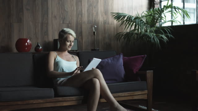 lone woman uses tablet on couch, medium shot - kamisol stock-videos und b-roll-filmmaterial