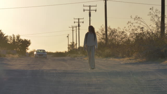 lone woman walks away from car driving down dirt road, low angle - ヒッチハイキング点の映像素材/bロール