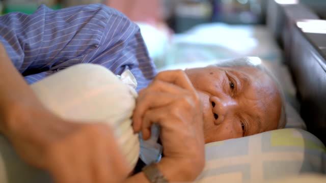 vídeos de stock, filmes e b-roll de solidão 4k homem asiático idoso na cama que grita em casa - condição médica