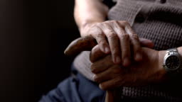loneliness senior man hand with walking stick sitting in dark room at home