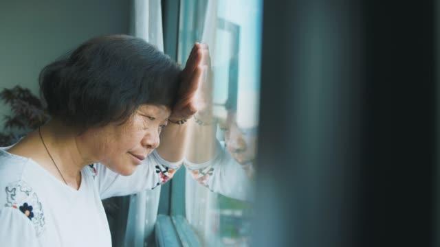 einsamkeit seniorin durch fenster - seniorinnen stock-videos und b-roll-filmmaterial
