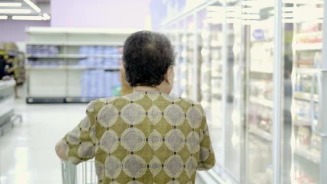 Solitude sénior femme achète de la nourriture en supermarché.