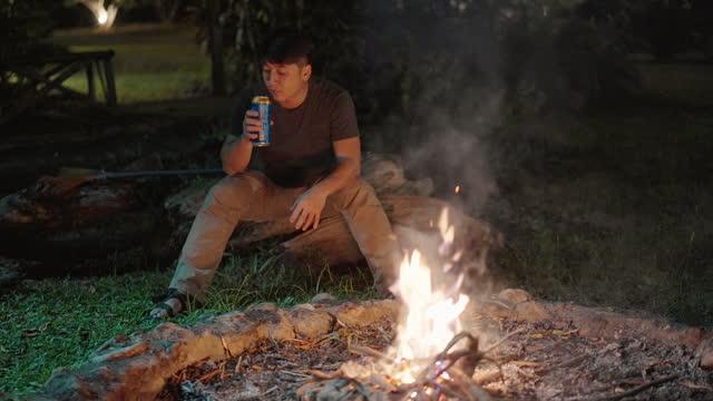 たき火でビールを飲む孤独なアサインの男 - 外乗点の映像素材/bロール