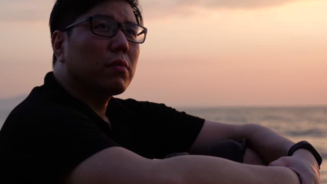 ビーチのそばに座っている孤独なアジア人男性 - fan palm tree点の映像素材/bロール