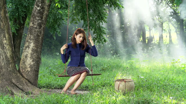 4K: Lonely Asian woman in Thai traditional costume sitting on a swing under the tree