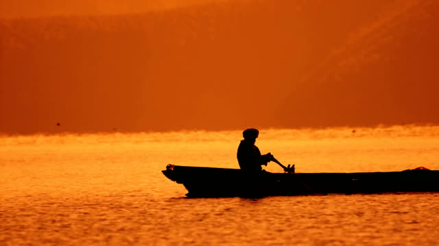 lonely boat and beautiful sunset - rowing stock videos & royalty-free footage