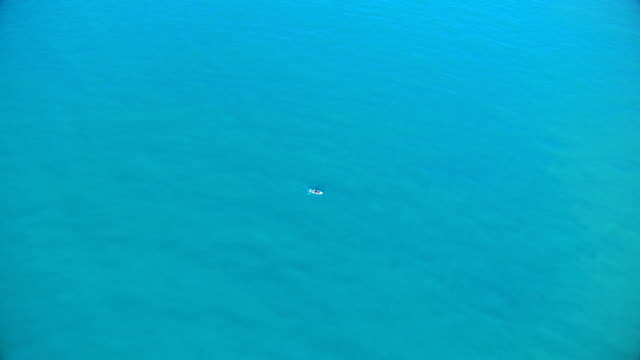 lonely boat in pacific ocean - turquoise colored stock videos & royalty-free footage