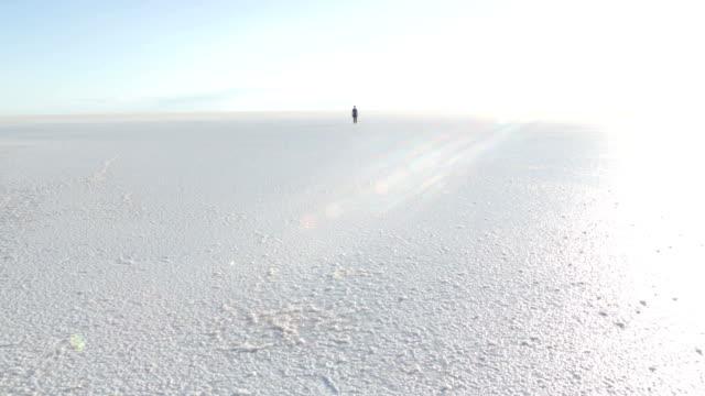 lonely boy walking on salt lake - approaching stock videos & royalty-free footage