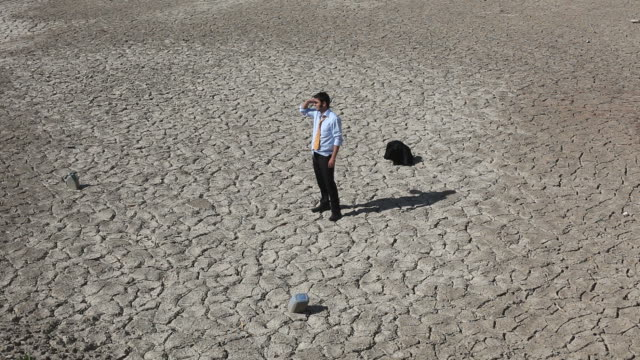 Lonely businessman is lost in desert and seek for help