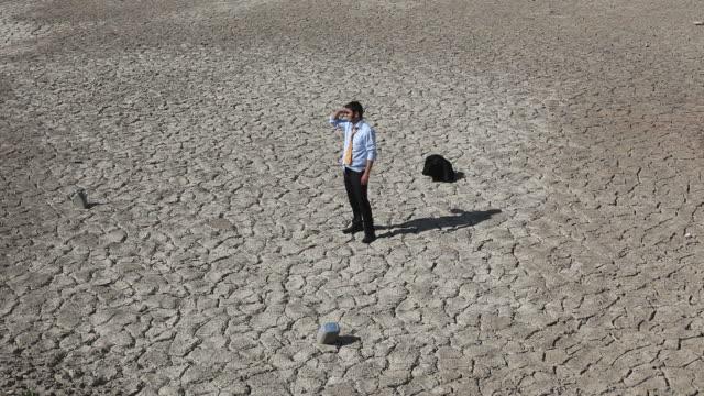 stockvideo's en b-roll-footage met lonely businessman is lost in desert and seek for help - selimaksan
